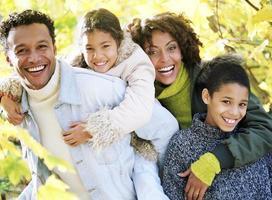 familj på fyra poserar i skogen foto