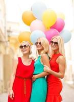 vackra flickor med färgglada ballonger i staden foto