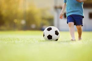 liten pojke som spelar fotboll foto