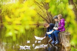 tre barn nära dammen som sätter pappersbåtar foto