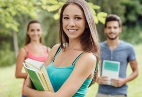 leende student poserar med anteckningsböcker foto