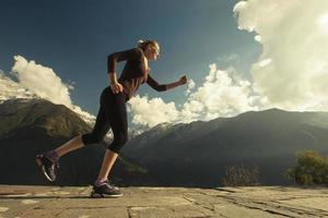 löpare för ung kvinna i vackert bergslandskap foto