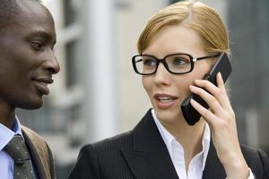 affärskvinna pratar i telefon, man ser på.