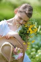 glad ung flicka som håller ett gäng sommarblommor foto
