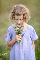 liten flicka med blommor i håret foto