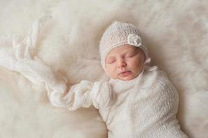 baby flicka som bär en vit stickad motorhuv foto