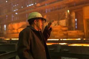 arbetar på den metallurgiska anläggningen foto