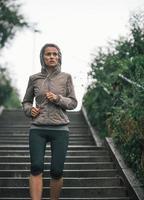 fitness ung kvinna som joggar i regnig stad foto