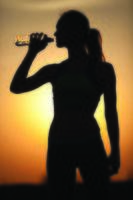 silhuett av en ung sportig kvinna dricksvatten foto