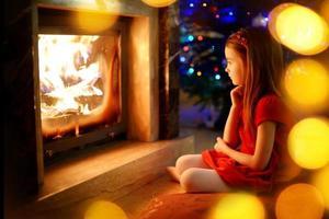glad liten flicka sitter vid en öppen spis på julafton foto