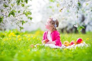 skrattande barnflicka som äter äpple i en blommande trädgård foto