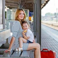 söt liten flicka och mamma på en järnvägsstation. foto