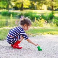 vacker liten flicka i regnstövlar som leker med gummi groda foto