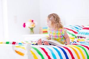 liten flicka som läser en bok i sängen foto