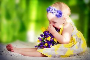 liten flicka med vårblommor foto
