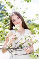 vacker flicka i en trädgård för körsbärsröd blomning