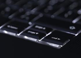 närbild av bakgrundsbelyst dator laptop tangentbord selektiv fokus slutknapp