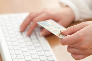 använder dator och kreditkort för online betalning foto