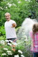 far och dotter som vattnar växter i trädgården foto