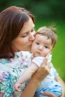 mamma kysser baby son, närbild, sommar foto