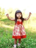 porträtt glad söt liten flicka med en röd klänning foto