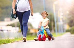 ung gravid mamma med liten dotter i park foto
