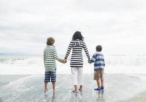 kvinna och två pojkar som tittar ut mot havet foto