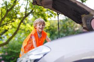 liten pojke tittar på motor i familjebil foto
