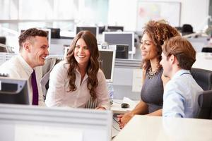 fyra unga kontorskollegor i ett tillfälligt lagmöte foto