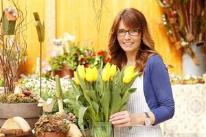 leende äldre kvinna blomsterhandlare ägare för blommor butik foto