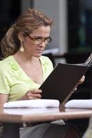 kvinna läser meny utanför restaurangen foto