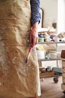 närbild av den kvinnliga konstnärinnehavborsten i studio