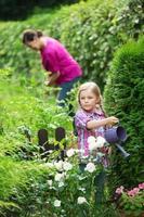 tjej som hjälper mormor i trädgården, vattenplanter foto