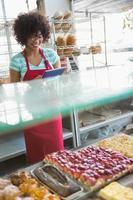 leende servitris med hjälp av TabletPC foto