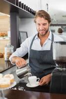 barista hälla mjölk i en kopp kaffe foto