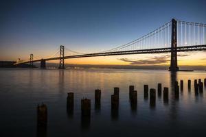 san francisco bay bridge vid soluppgången foto
