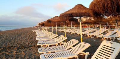 solstol och strandparaply på ensam sandstrand. foto