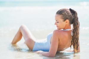 avslappnad ung kvinna i baddräkt som ligger vid havet. bakåtsikt foto