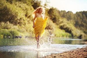 vacker ung kvinna strö vatten i floden foto