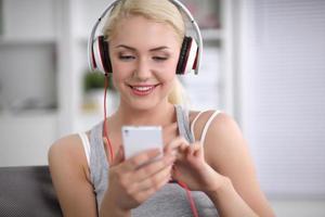 ung vacker kvinna hemma sitter på soffan och lyssnar foto
