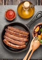 grillade korvar i en panna och grönsaksallad. foto