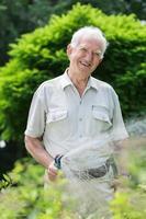 äldre trädgårdsmästare med hosepipe foto
