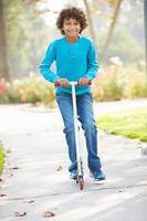 ung pojke som rider på skoter i parken