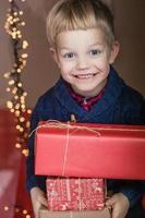 porträtt av bedårande barn med presentförpackning. jul. födelsedag foto