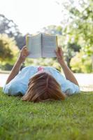 vacker kvinna läser bok i parken foto