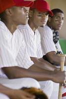 basebollspelare som sitter i dugout foto