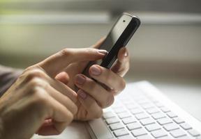 smartphone och datortangentbord till hands. foto