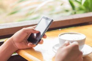 närbild hand använda smart telefon och håll kaffe