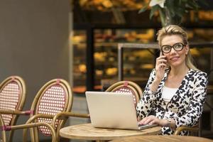 attraktiv kvinna som pratar på mobil medan man sitter med en bärbar dator foto