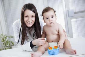 baby och läkare foto
